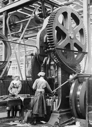 Two women munition workers operate a shell case forming